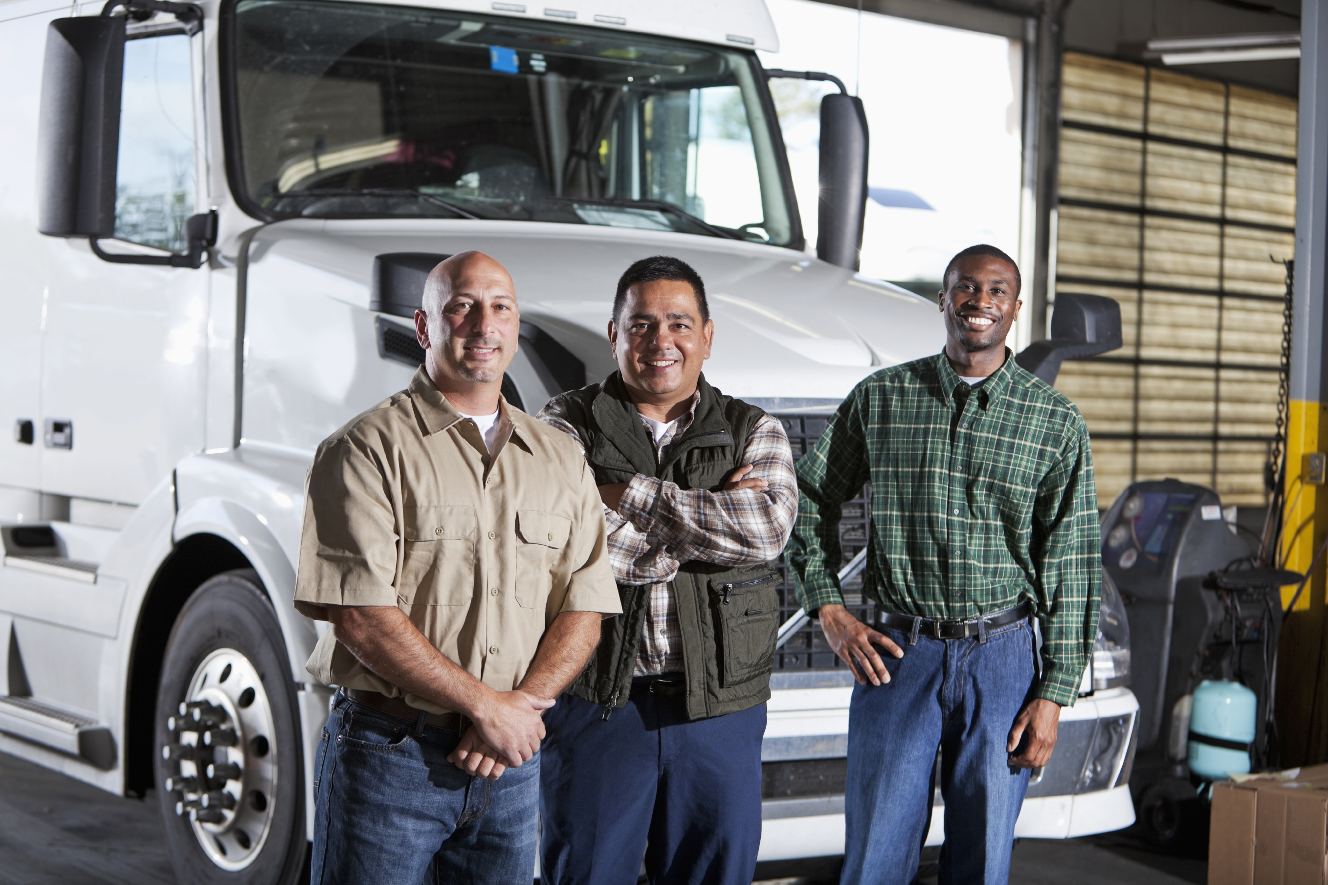 Multi-ethnic men with semi-truck.